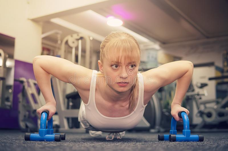 Sport. Beautiful woman in the gym, Cute cute blonde while doing push-UPS on a special push-up simulator, crossfit royalty free stock photo