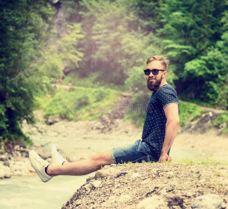 Sport bemannt mit einem Bart und einem guten Haarschnitt in der Sonnenbrille und in den kurzen Hosen, das Lächeln und sitzt auf d lizenzfreie stockbilder
