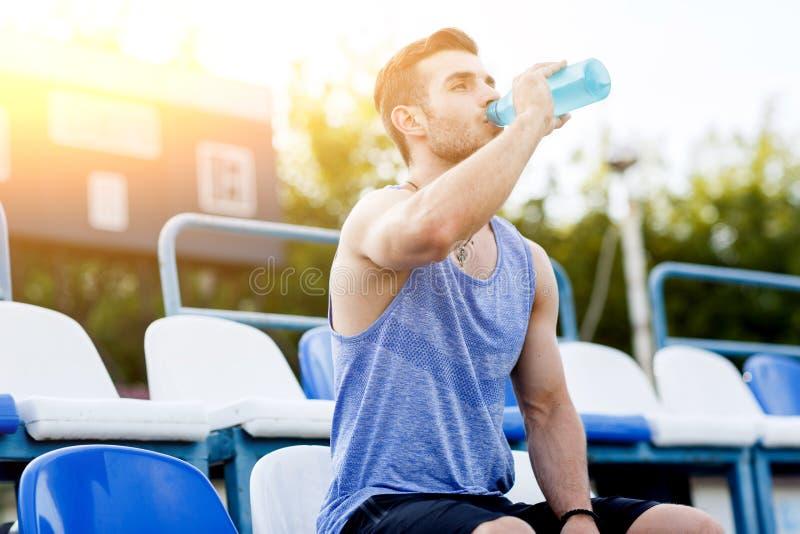 Sport bemannt Trinkwasser, nachdem sie auf Freienstadion trainiert haben lizenzfreie stockbilder