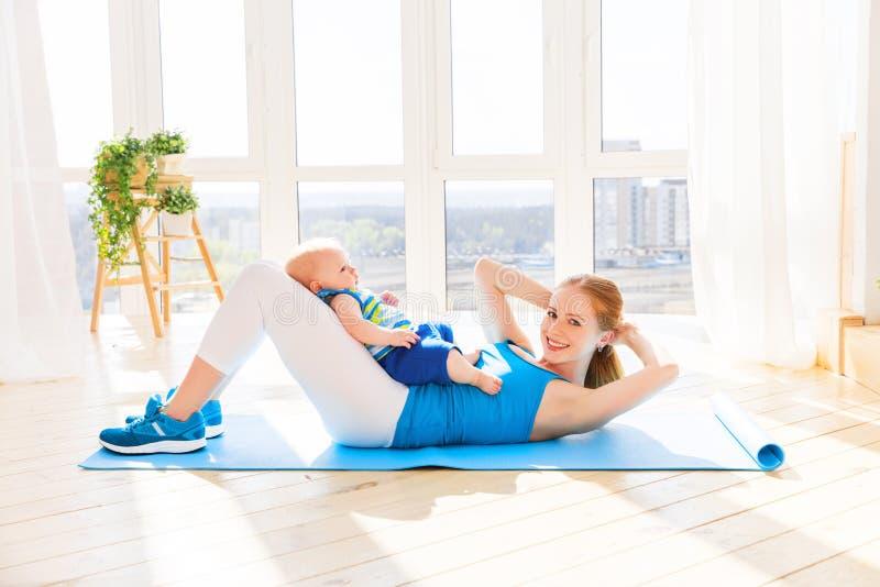 Sport bemuttert teilnimmt an Eignung und Yoga mit Baby zu Hause stockbild
