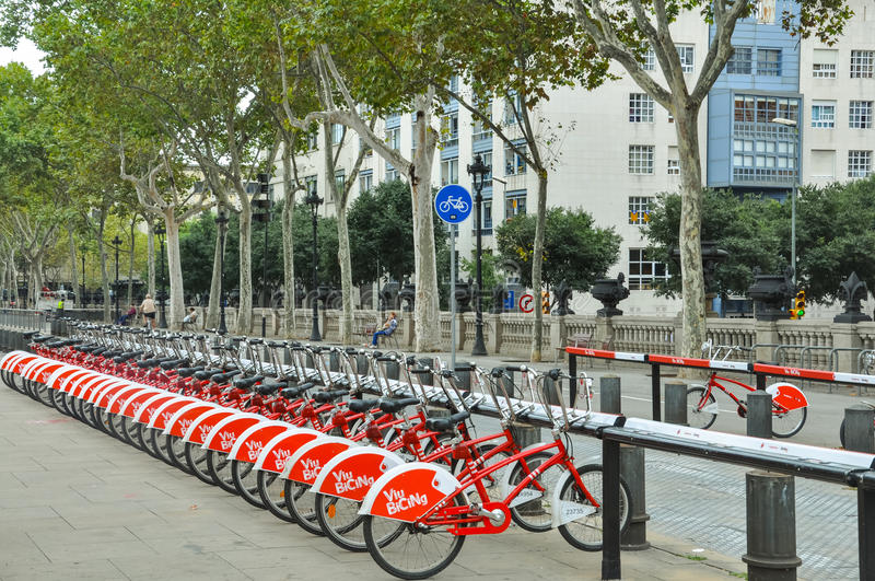 Sport, bicycling, healthy lifestyle, city transport concept. Number of red bikes for rent in Barcelona, Spain. Blue road sign on b royalty free stock image