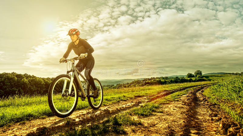 Sport bike woman on a meadow with a beautiful landscape.  royalty free stock photography