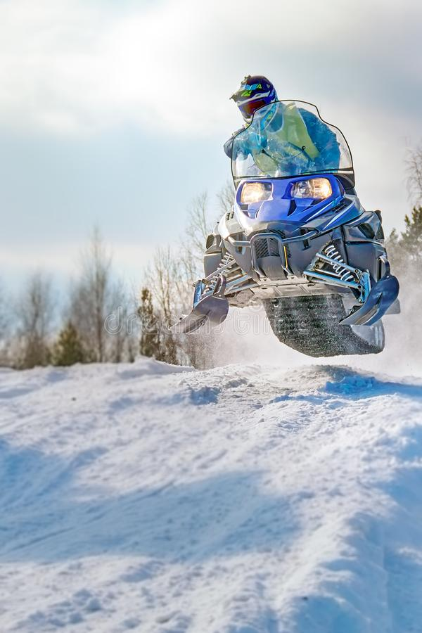 Sport blue snowmobile jump. Cloud of snow dust from under snowmobile tracks. Front view, vertical shot. stock photos