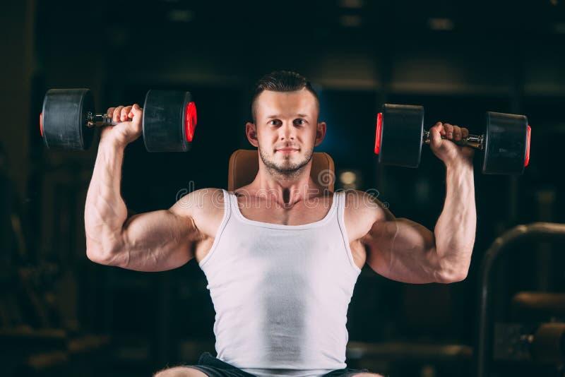 Sport, Bodybuilding, Gewichtheben, Lebensstil und Leutekonzept - junger Mann mit den Dummköpfen, die Muskeln in der Turnhalle bie lizenzfreie stockfotografie