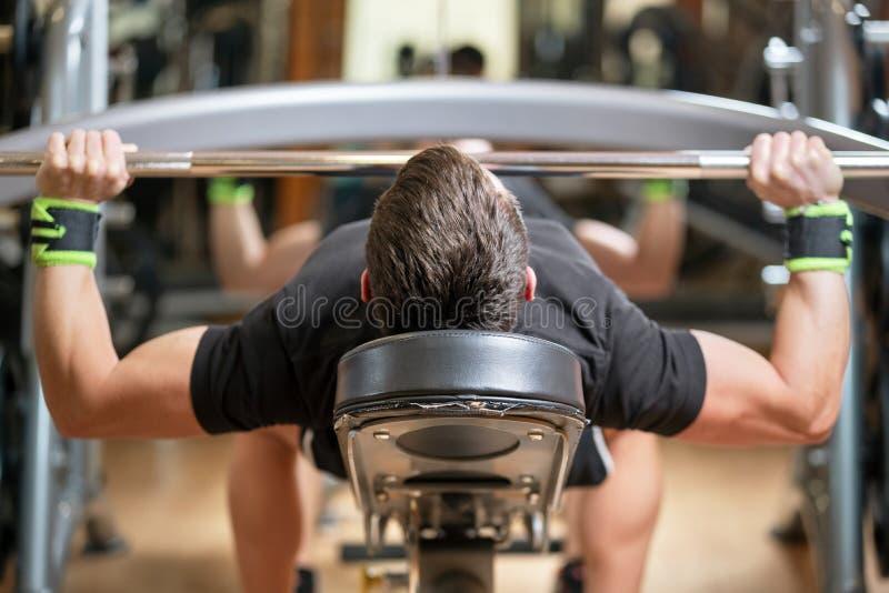Sport, Bodybuilding, Lebensstil und Leutekonzept - junger Mann mit dem Barbell, der Muskeln biegt und Bank macht, dr?cken Turnhal lizenzfreies stockbild
