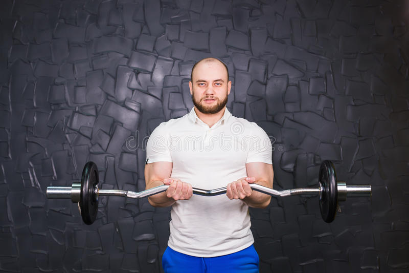 Sport, bodybuilding, lifestyle and people concept - smiling man with barbell.  stock photo
