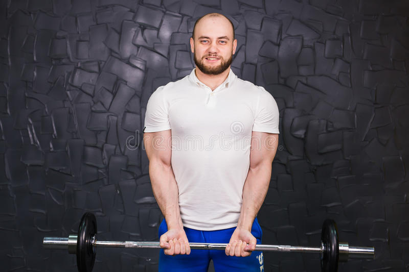 Sport, bodybuilding, lifestyle and people concept - smiling man with barbell.  stock images