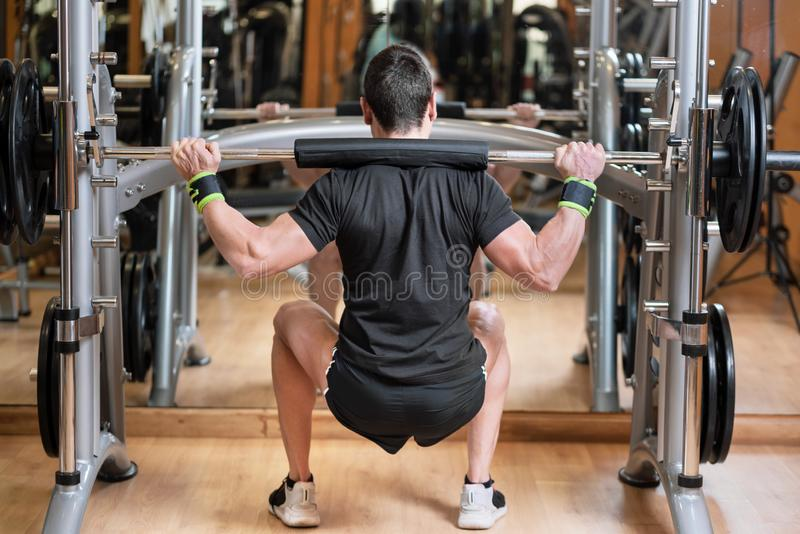 Sport, bodybuilding, lifestyle and people concept - young man with barbell doing squats in gym. royalty free stock photography