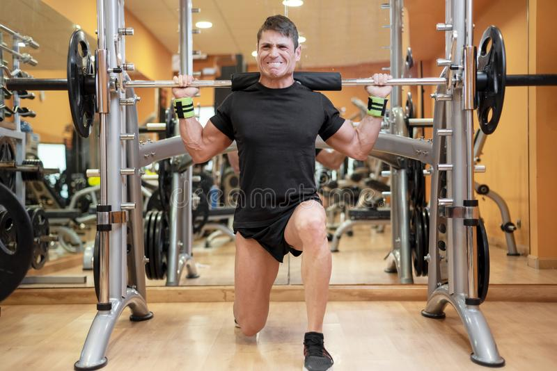 Sport, bodybuilding, lifestyle and people concept - young man with barbell doing squats in gym. royalty free stock images