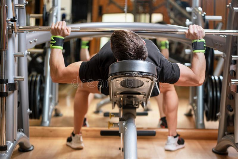 Sport, bodybuilding, lifestyle and people concept - young man with barbell flexing muscles and making bench press in gym royalty free stock photos