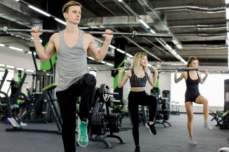 Sport, bodybuilding, livsstil och folkbegrepp - ung man och två kvinnor med skivstången som böjer muskler och framställning royaltyfria bilder