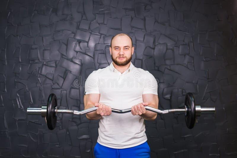 Sport, bodybuilding, styl życia i ludzie pojęć, - uśmiechnięty mężczyzna z barbell zdjęcie stock