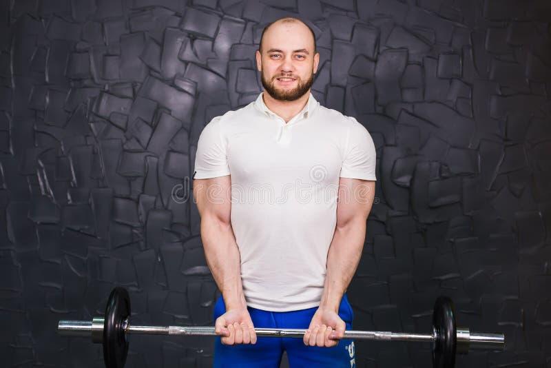 Sport, bodybuilding, styl życia i ludzie pojęć, - uśmiechnięty mężczyzna z barbell obrazy stock