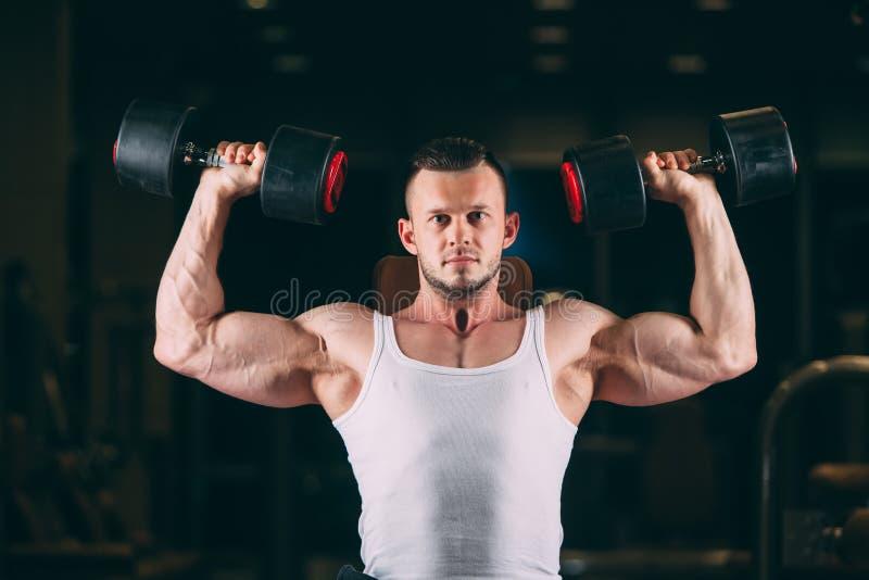 Sport, bodybuilding, tyngdlyftning, livsstil och folkbegrepp - ung man med hantlar som böjer muskler i idrottshall fotografering för bildbyråer