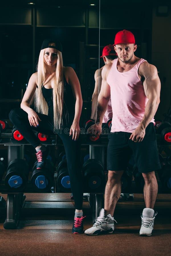 Sport, bodybuilding, tyngdlyftning, livsstil och folkbegrepp - ungt härligt par i stilfull kläder som sitter a royaltyfri fotografi