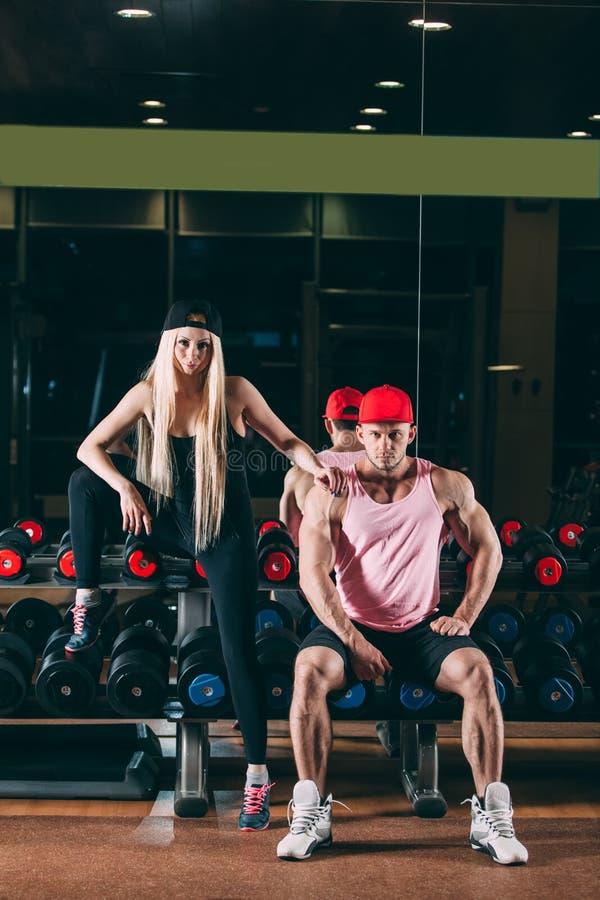 Sport, bodybuilding, tyngdlyftning, livsstil och folkbegrepp - ungt härligt par i stilfull kläder som sitter a fotografering för bildbyråer