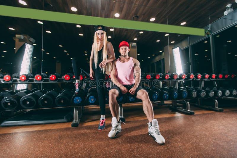 Sport, bodybuilding, tyngdlyftning, livsstil och folkbegrepp - ungt härligt par i stilfull kläder som sitter a arkivfoton
