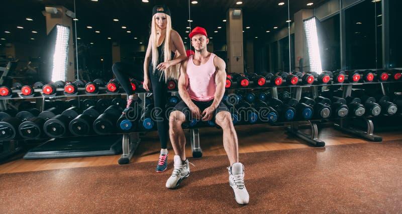 Sport, bodybuilding, tyngdlyftning, livsstil och folkbegrepp - ungt härligt par i stilfull kläder som sitter a arkivfoto