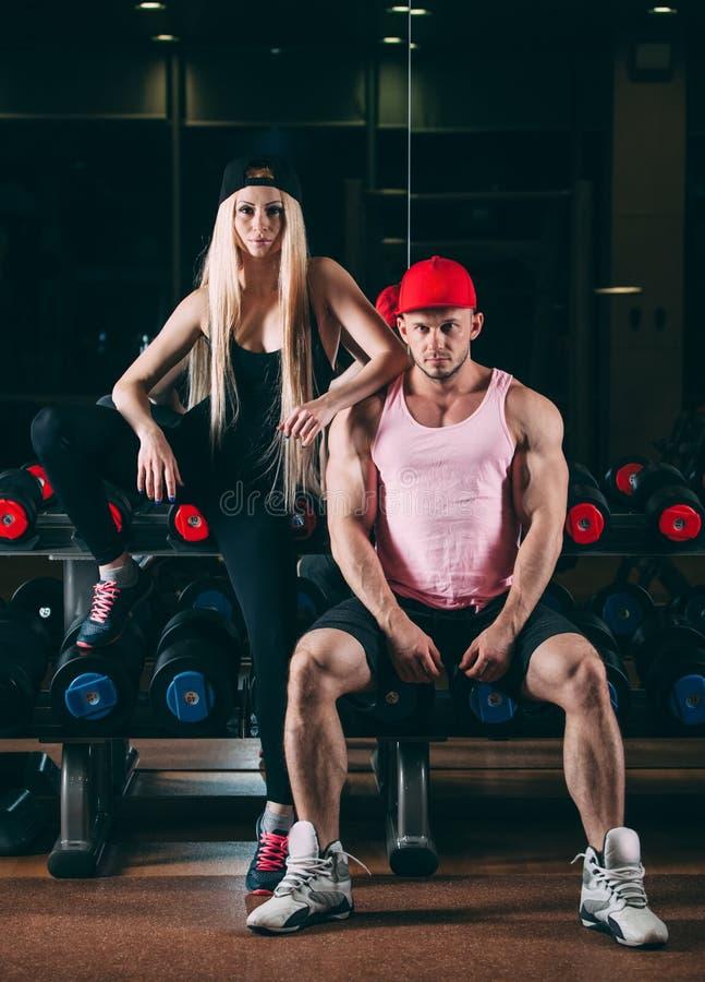 Sport, bodybuilding, tyngdlyftning, livsstil och folkbegrepp - ungt härligt par i stilfull kläder som sitter a royaltyfria foton
