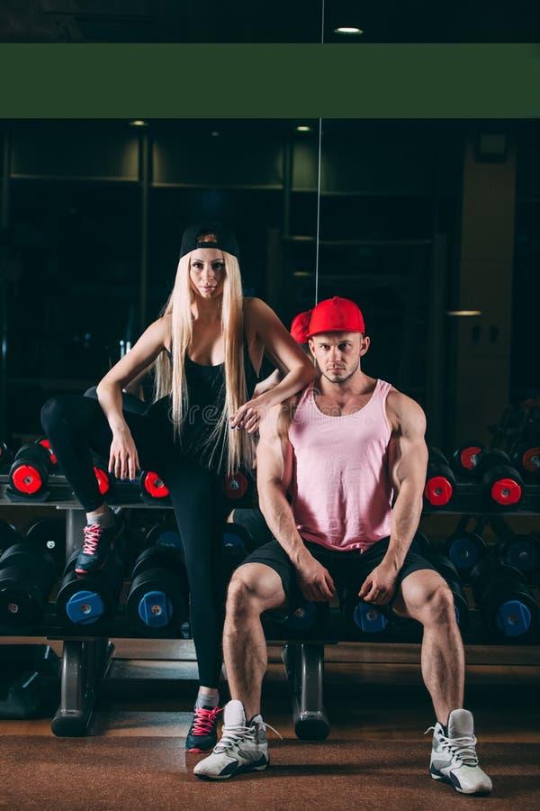 Sport, bodybuilding, tyngdlyftning, livsstil och folkbegrepp - ungt härligt par i stilfull kläder som sitter a arkivbilder
