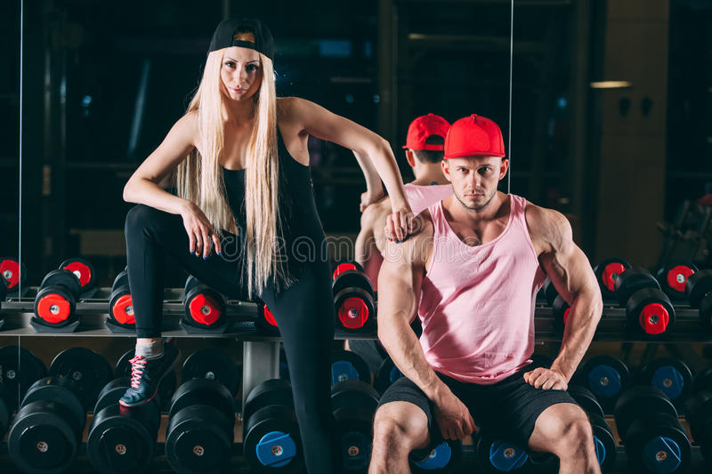 Sport, bodybuilding, weightlifting, lifestyle and people concept - Young beautiful couple in stylish clothes sitting a royalty free stock image