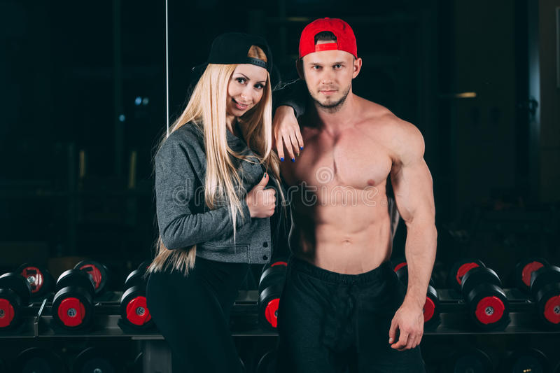 Sport, bodybuilding, weightlifting, lifestyle and people concept - Young beautiful couple in stylish clothes sitting a. Sport, bodybuilding, weightlifting stock image