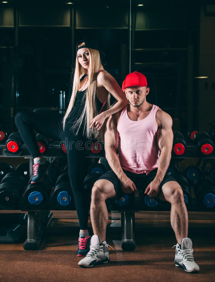 Sport, bodybuilding, weightlifting, lifestyle and people concept - Young beautiful couple in stylish clothes sitting a royalty free stock photo