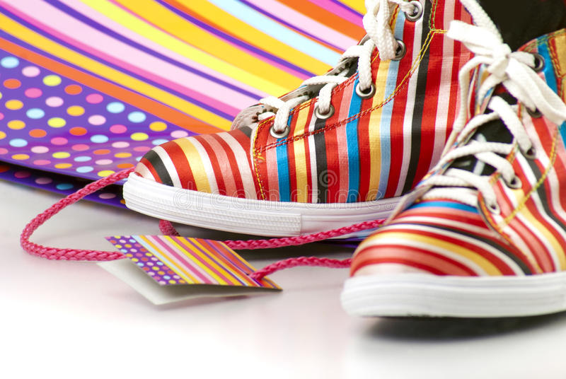 Sport chic. Pair of colorful striped gym-shoes with shopping bag royalty free stock photos