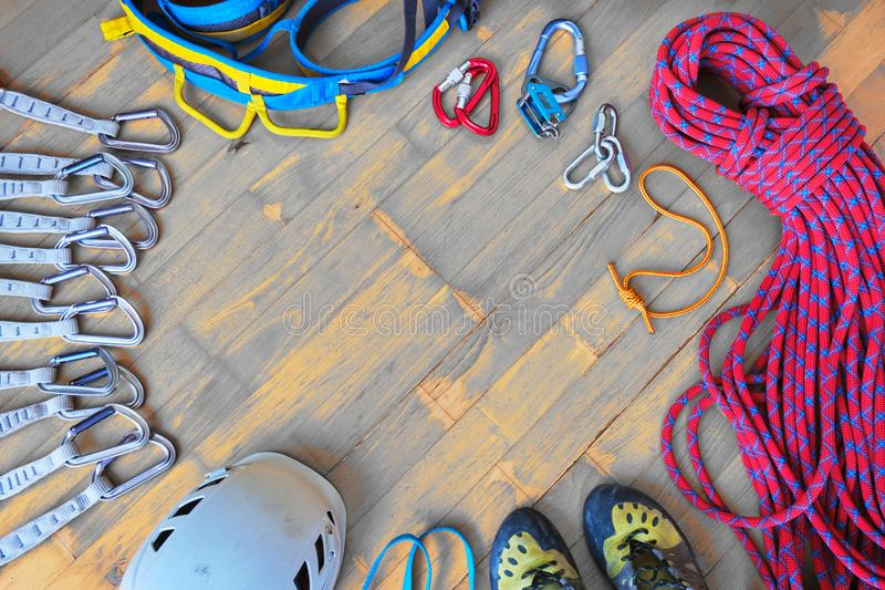 Sport climbing gear with space for text in the middle - top down view, wooden background. Set of: quickdraws, helmet, harness. royalty free stock photos