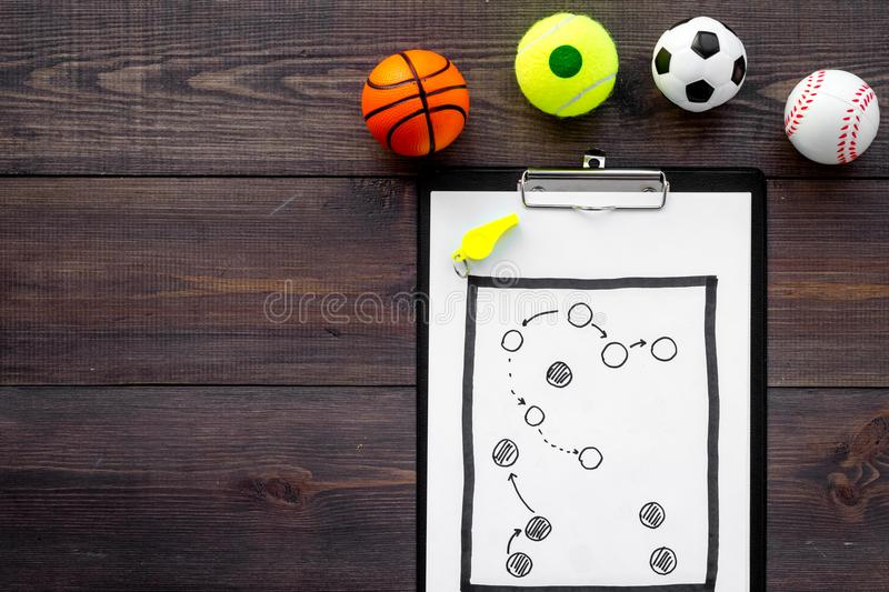 Sport coach concept. Pad with tactic plan of the match near whistle and balls on wooden background top view copy space stock image