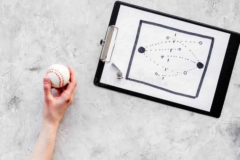 Sport coach concept. Pad with tactic plan of the match near whistle and base-ball ball on stone background top view copy royalty free stock images