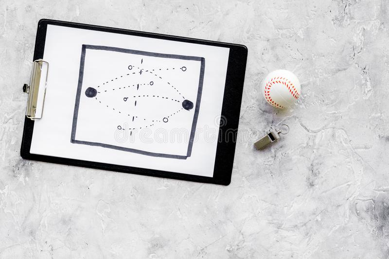 Sport coach concept. Pad with tactic plan of the match near whistle and base-ball ball on stone background top view copy stock images