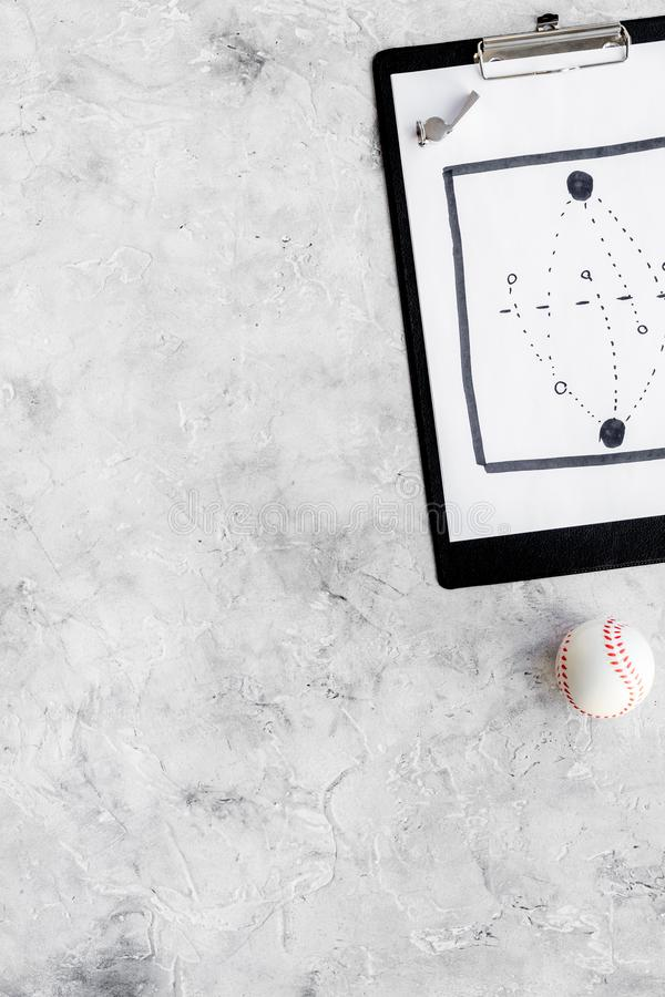 Sport coach concept. Pad with tactic plan of the match near whistle and base-ball ball on stone background top view copy royalty free stock photo