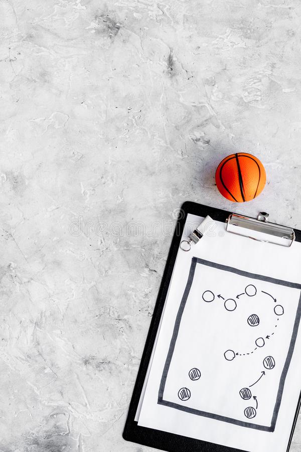 Sport coach concept. Pad with tactic plan of the match near whistle and basketball ball on stone background top view royalty free stock photo