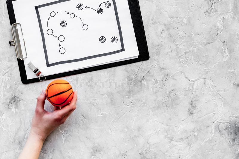 Sport coach concept. Pad with tactic plan of the match near whistle and basketball ball on stone background top view stock photography
