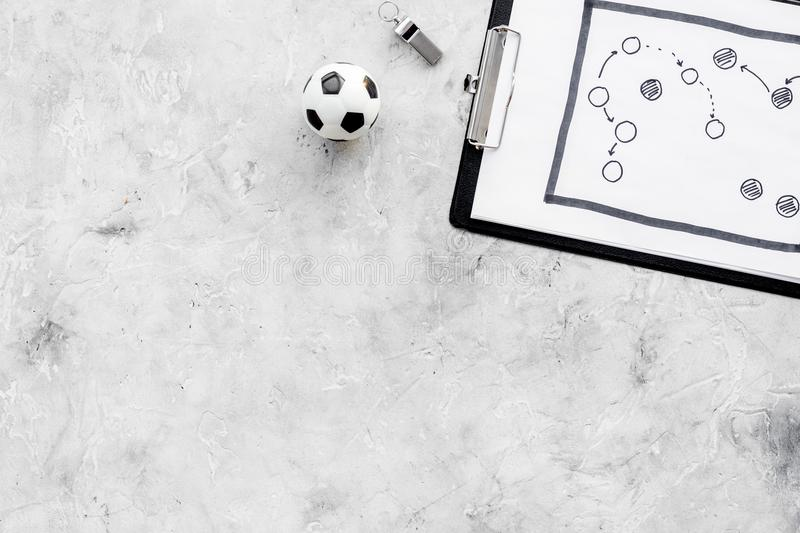 Sport coach concept. Pad with tactic plan of the match near whistle and football ball on stone background top view copy royalty free stock image