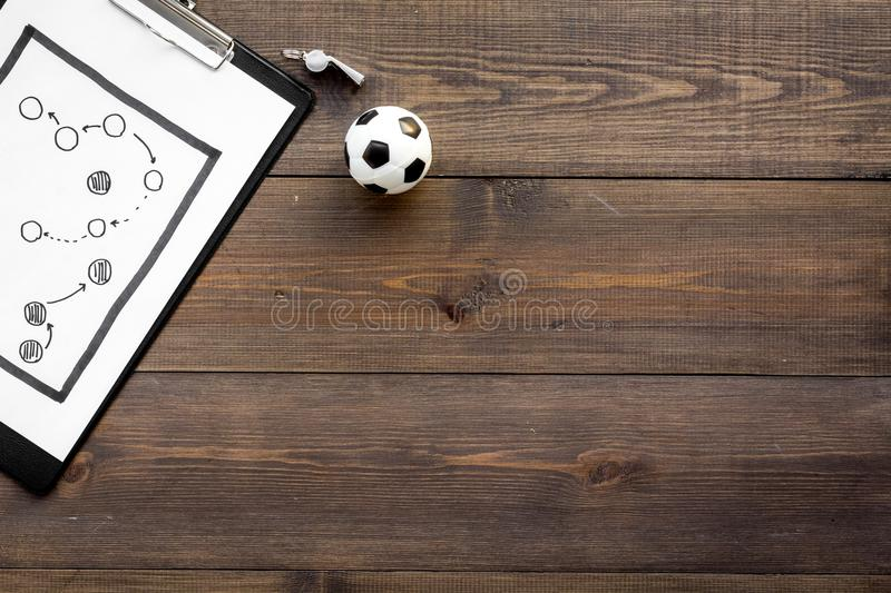 Sport coach concept. Pad with tactic plan of the match near whistle and football ball on wooden background top view copy royalty free stock photography