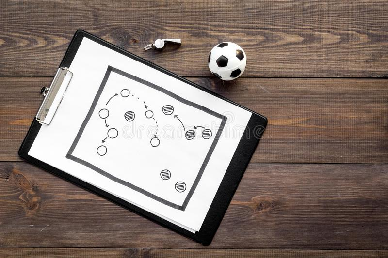 Sport coach concept. Pad with tactic plan of the match near whistle and football ball on wooden background top view copy stock photos
