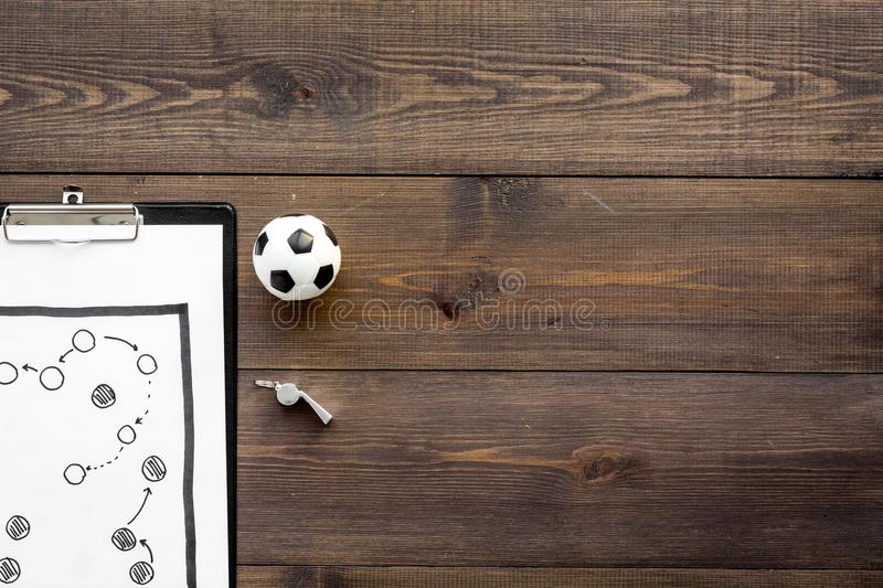 Sport coach concept. Pad with tactic plan of the match near whistle and football ball on wooden background top view copy stock image