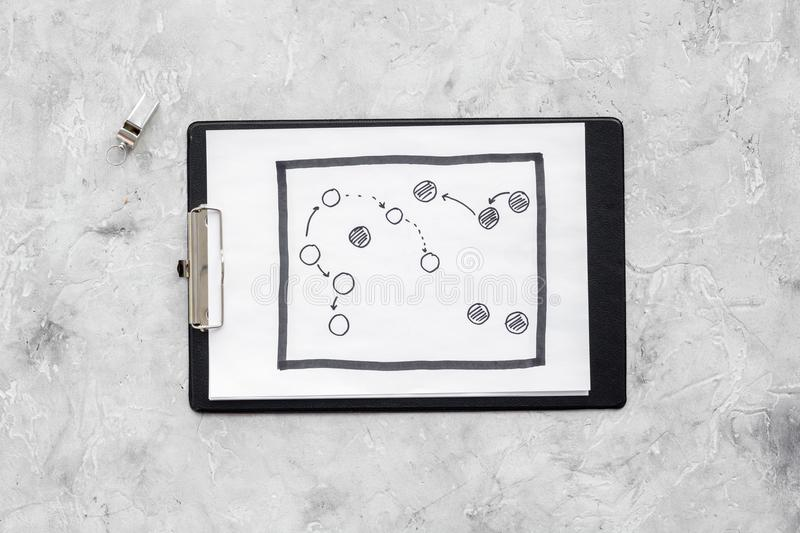 Sport coach concept. Pad with tactic plan of the match near whistle stone background top view copy space stock photo