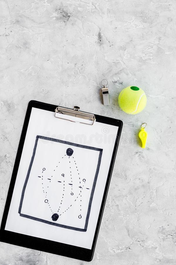 Sport coach concept. Pad with tactic plan of the match near whistle and tennis ball on stone background top view copy stock images