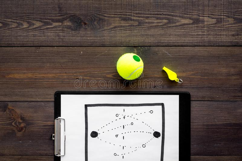 Sport coach concept. Pad with tactic plan of the match near whistle and tennis ball on wooden background top view copy stock photo
