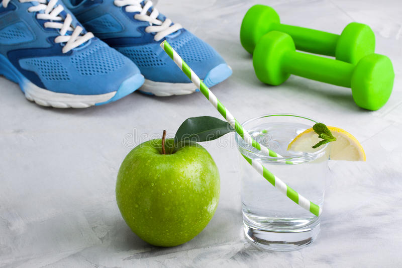 Sport composition with sports equipment glass water apple royalty free stock photos