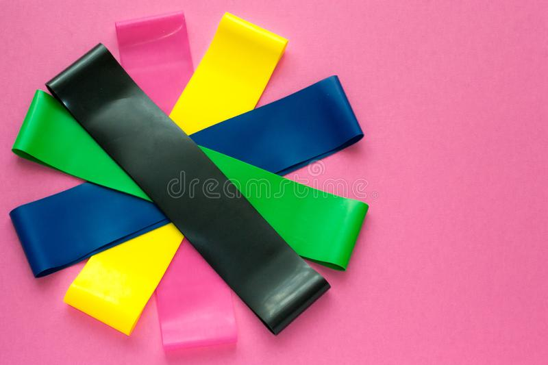 Sport concept - colorful fitness gums for woman training on pink background. Slimming process with cardio training. Equipment for. Sport concept - colorful stock photography