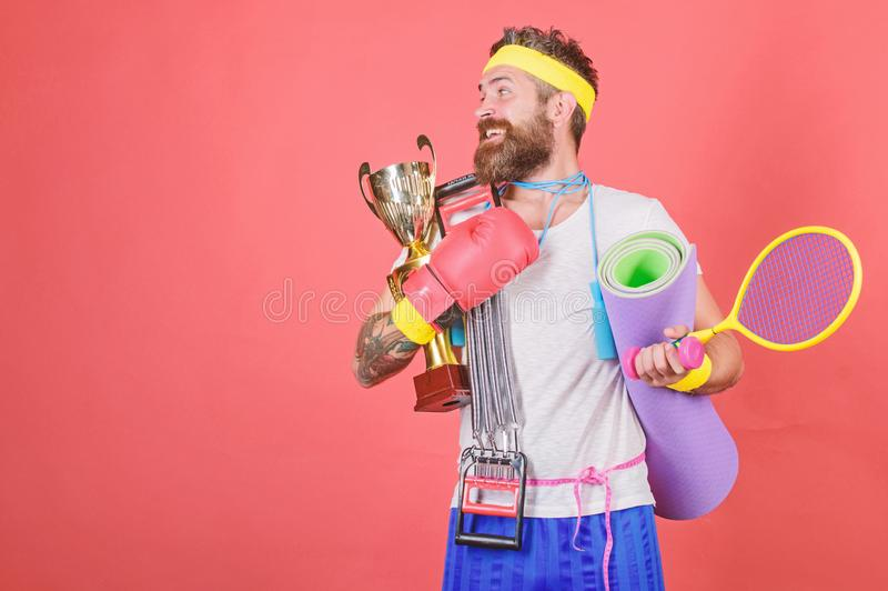 Sport concept. Get body ready for summer. Choose sport you like. Man bearded athlete hold sport equipment jump rope. Fitness mat boxing glove expander racket royalty free stock photography