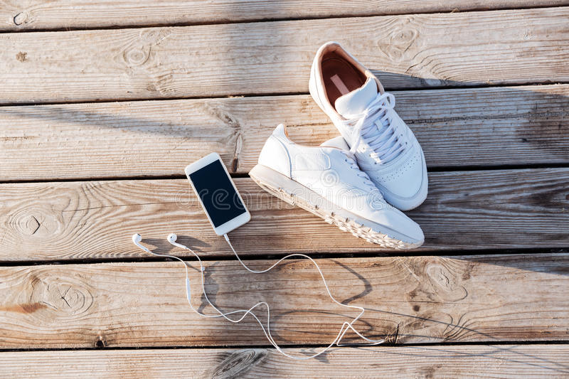 Sport concept - pair of white sneakers, smartphone and earphones royalty free stock images