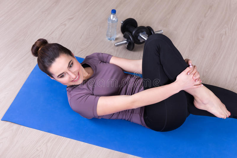 Sport concept - top view of slim woman doing stretching exercise. S on the floor at home stock image