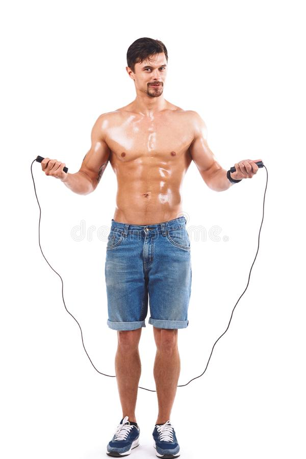 Portrait of young male athlete with skipping rope, Isolated over. Sport concept of young male athlete with skipping rope stock photo
