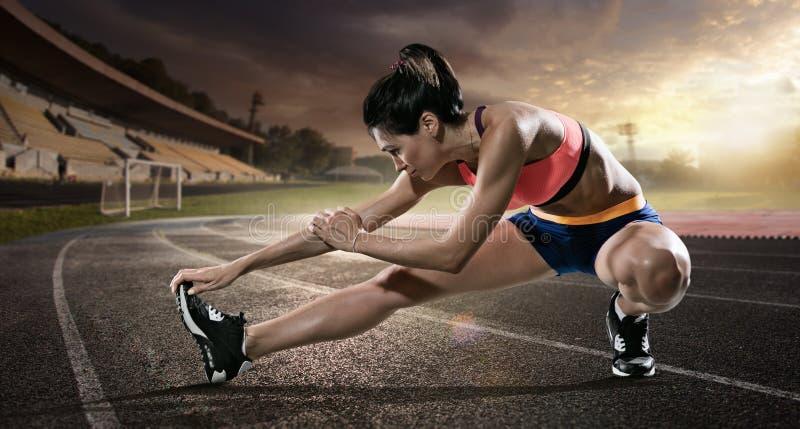 sport Corridore che allunga sulla pista corrente immagine stock libera da diritti