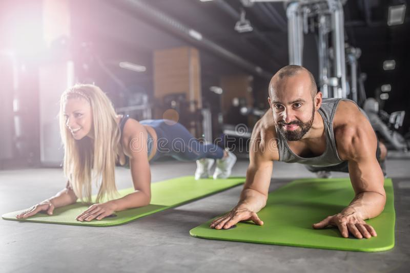 Sport couple doing plank exercise workout in fitness centrum. Man and woman practicing plank in the gym stock photography